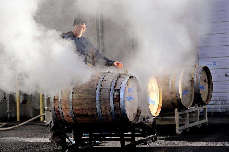 In this photo taken Thursday, Nov. 21, 2019, cellar master Jim Hewitson applies steam to wine barrels to hydrate and seal them before wine is added at Patterson Cellars winery in Woodinville, Wash. Washington, which now boasts more than 1,000 wineries in the state, has become a force in the wine industry. The state is the second-largest producer of premium wines in the United States, trailing only California. (AP Photo/Elaine Thompson)