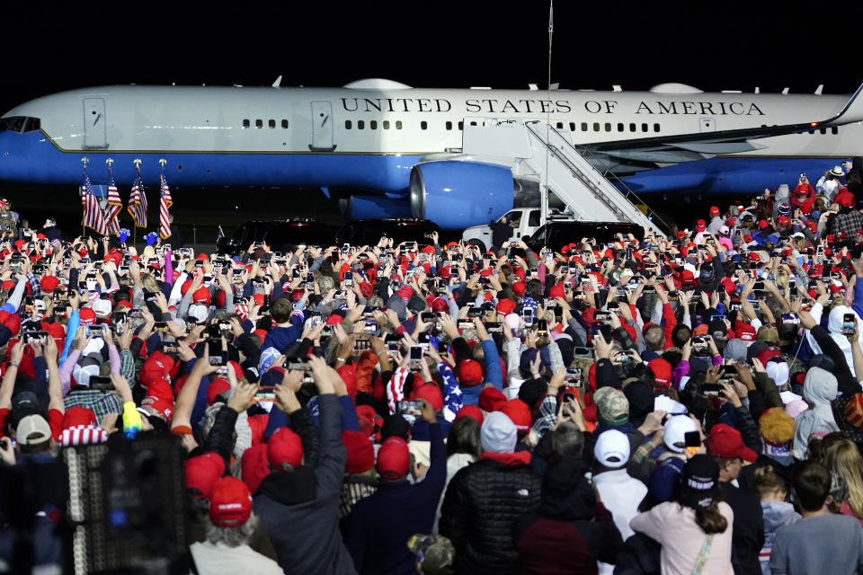 Supporters cheer as Air Force One with President Donald Trump arrives at at a campaign rally.