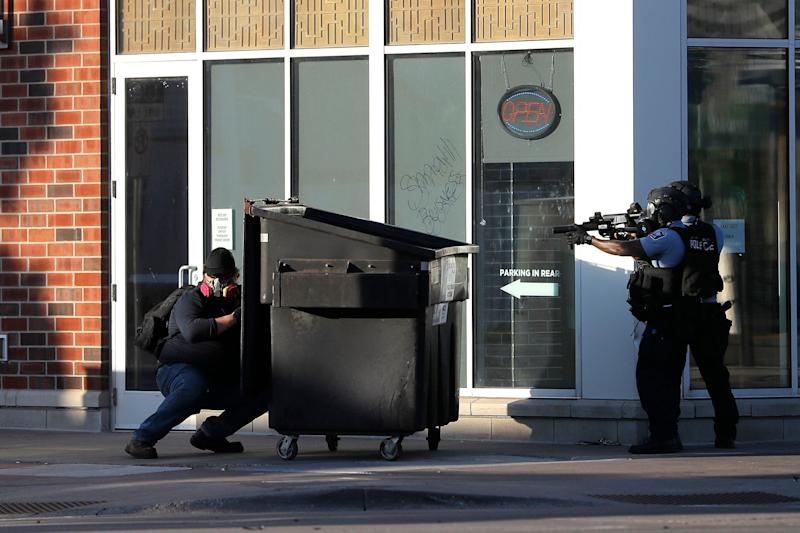 <strong>A protester hides behind a dumpster he pulled as a barrier while St. Paul Police officers move in to retrieve it.</strong> (Photo: ASSOCIATED PRESS)