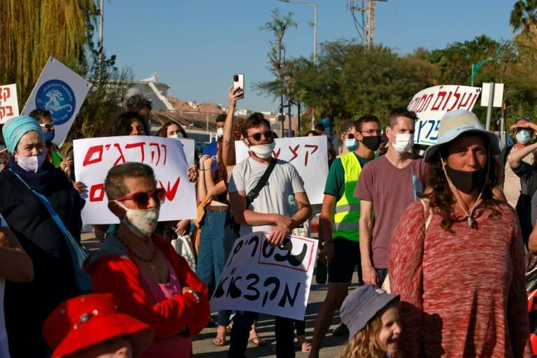 Environmental activists gather for a protest at a parking lot overlooking an oil jetty in the port city of Eilat