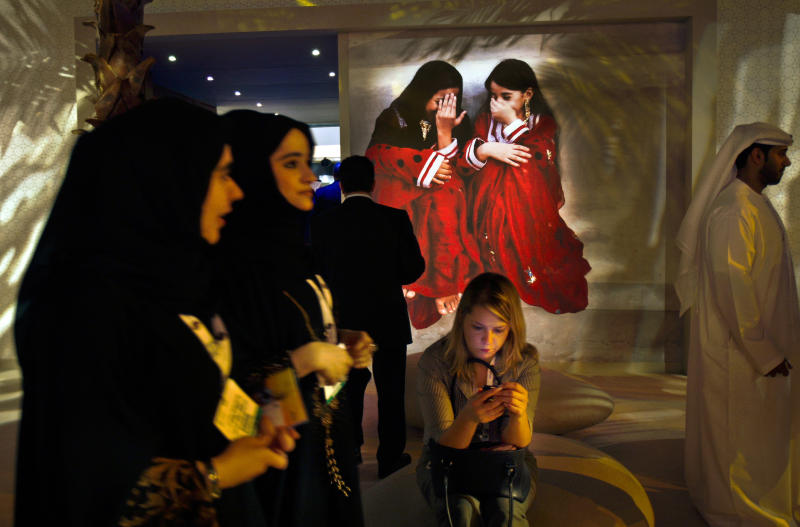 In this Tuesday, May 5, 2009 photo, young Emirati staff members in plain black outfits pass by a western woman visitor and a poster showing two Khaliji girls during the Arab Travel Market exhibition in Dubai, United Arab Emirates. Just a few years ago, Gulf Arab women usually only felt comfortable showing off their fashion sense at ladies-only parties or family gatherings. In public, at least in their home countries, the standard all-black abaya _ a simple floor-length covering and accompanying head scarf _ was the only culturally accepted option. But now a new generation of abaya designers are giving the traditional garment a twist with choices of fabric, designs and even some expensive bling to allow Gulf women a host of style options. (AP Photo/Kamran Jebreili)