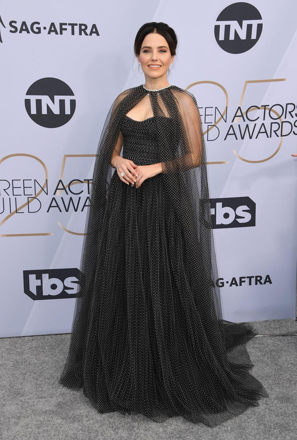 <p>Wearing a Monique Lhuillier cape gown with a Jimmy Choo purse and Jacob & Co. Jewelry.</p>