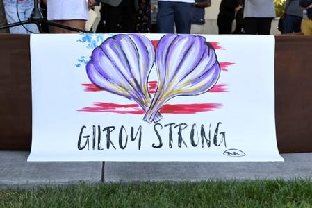 "A painting by Gilroy resident Ignacio ""Nacho"" Moya on the stage at a vigil for those who died and were injured at the mass shooting at the Gilroy Garlic Festival"