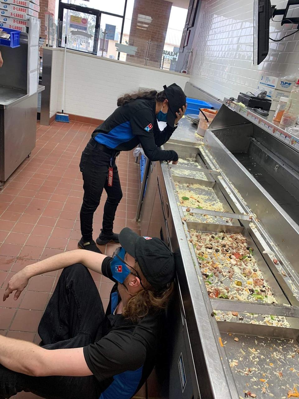 Two Domino's workers tired after a four hours of working and running our of food.