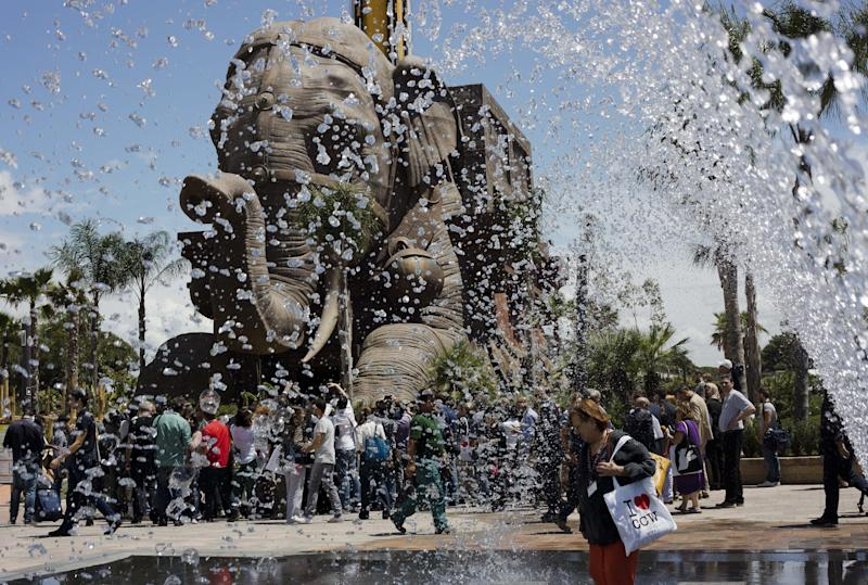 """In this July 10, 2014 photo, journalists gather in front of a gigantic elephant statue part of the adventurous family ride """"Erawan - The lost Temple"""", a 54 meter drop tower, as they visit the Cinecitta World theme park in the outskirts of Rome. Cinecitta World is a theme park, inspired to the Cinecitta film studios in Rome. Academy Award winning art director Dante Ferretti designed the attractions at the 500 million Euros (680 million US dollars) park that opened to the public on July 24. (AP Photo/Domenico Stinellis)"""