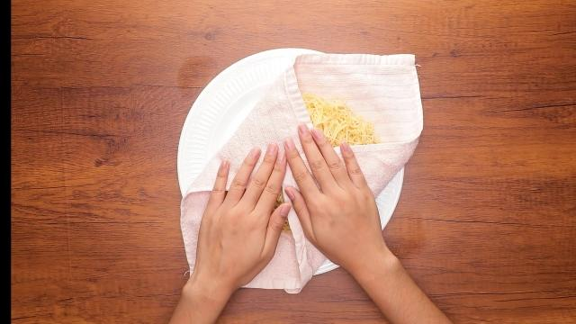 Pressing kitchen cloth over cooked noodles