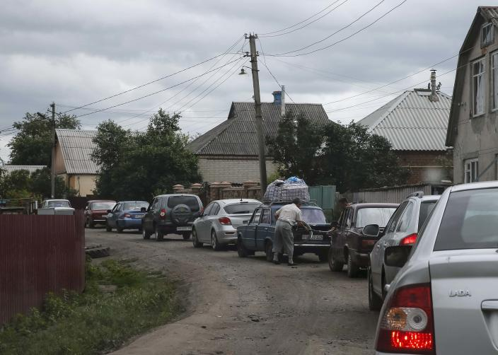 Local residents fleeing from the fighting in eastern Ukraine are seen in a line of cars near the town of Slaviansk June 12, 2014. Ukraine's new president signaled on Wednesday he would be ready to hold talks with opponents in eastern Ukraine if pro-Russian separatists waging an insurgency there agreed to lay down their weapons. REUTERS/Gleb Garanich (UKRAINE - Tags: POLITICS CIVIL UNREST)