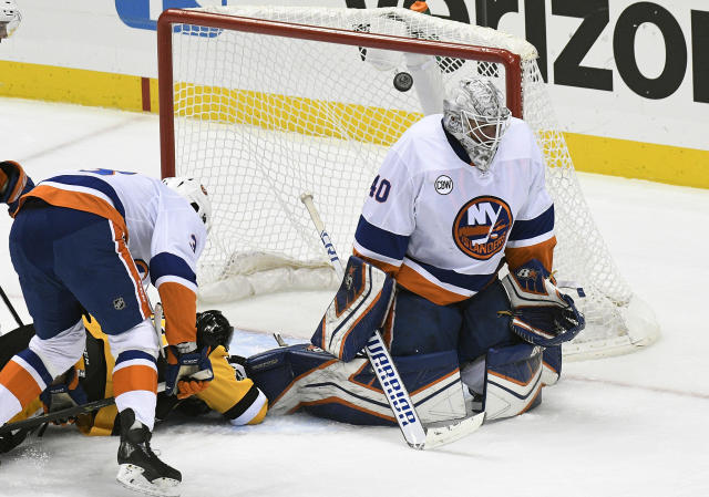 Pittsburgh Penguins center Riley Sheahan (15) shoots the puck off of the crossbar against New York Islanders goaltender Robin Lehner (40) during the first period of an NHL hockey game in Pittsburgh, Tuesday, Oct. 30, 2018 . (AP Photo/Don Wright)