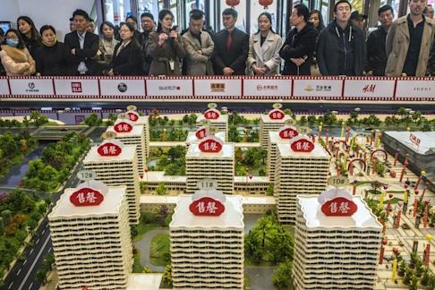 Prospective customers look at a model of the Dalian Wanda Group's Oriental Movie Metropolis at a showroom in Qingdao. Photo: Bloomberg