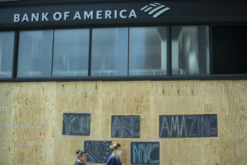"""MANHATTAN, NY - JUNE 06: One person wearing a mask and another not wearing a mask walk a Bank of American branch that has been boarded up and has art work on the boards that says, """"You Are Amazing NYC"""" with a heart. Many stores around New York have been boarded up based the on vandalism and looting that has occurred over the past few nights. In response, Mayor Bill de Blasio has put New York City is under a curfew that starts at 8 PM daily. Protesters keep taking to the streets across America and around the world after the killing of George Floyd at the hands of a white police officer Derek Chauvin that was kneeling on his neck during his arrest as he pleaded that he couldn't breathe. The protest are attempting to give a voice to the need for human rights for African American's and to stop police brutality against people of color. Many people were wearing masks and observing social distancing due to the coronavirus pandemic. Photographed in the Manhattan Borough of New York on June 06, 2020, USA. (Photo by Ira L. Black/Corbis via Getty Images)"""