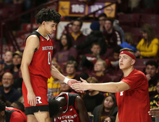 Rutgers guard Geo Baker (0) is congratulated by teammate Luke Nathan as he leaves late in the second half against Minnesota during a NCAA college basketball game Saturday, Jan. 12, 2019, in Minneapolis. Minnesota defeated Rutgers 88-70. (AP Photo/Andy Clayton-King)