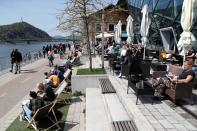Guests enjoy the sunny weather as they sit in front of a bistro after the Hungarian government allowed to reopen outdoor terraces in Budapest