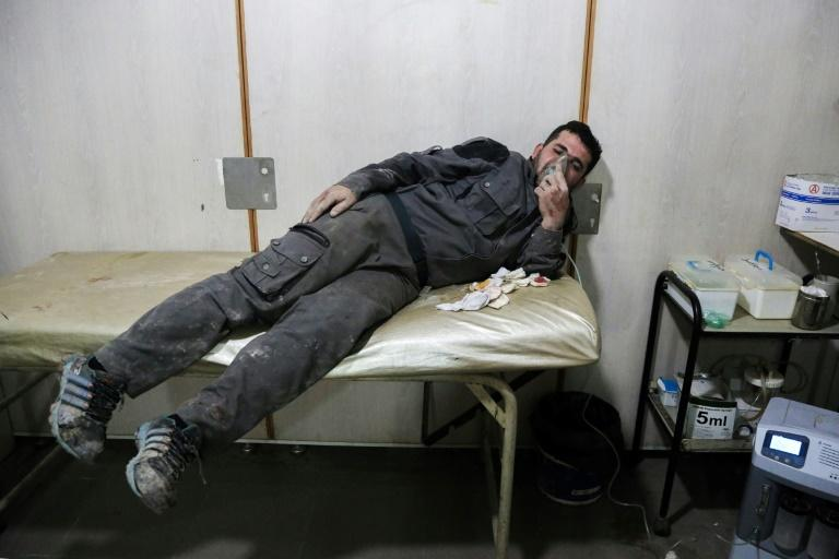 An injured Syrian breathes through an oxygen mask after a reported air strike in the rebel-controlled town of Hammuriyeh, on the outskirts of the capital Damascus, on March 25, 2017