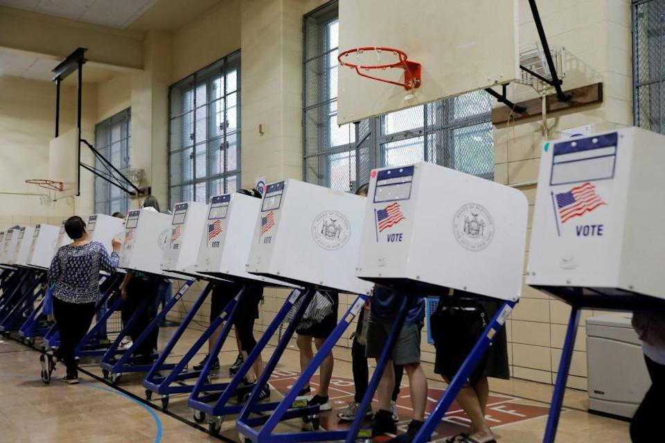People stand in privacy booths as they fill ballots at PS 250 during the New York City primary mayoral election in Brooklyn.