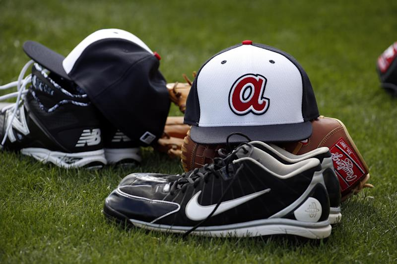 A new style Atlanta Braves hat sits on a glove during a spring training baseball workout, Thursday, Feb. 13, 2014, in Kissimmee, Fla. (AP Photo/Alex Brandon)