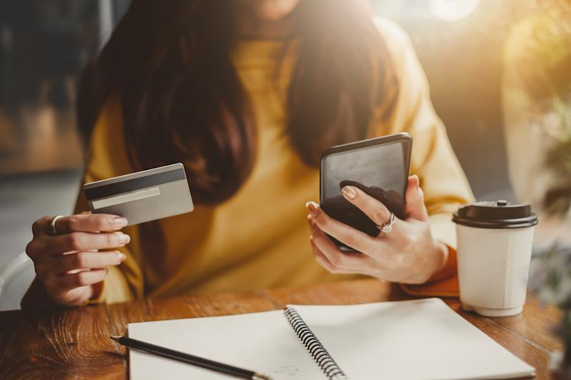 Woman holding a credit card and smartphone