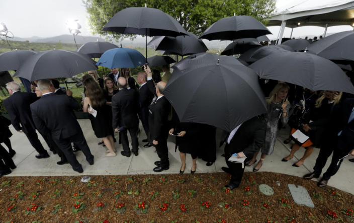 <p>People wishing to pay their respects wait in the rain during the graveside service for Nancy Reagan on the grounds of the Ronald Reagan Presidential Library.<i> (Photo: Chris Carlson/AP)</i></p>