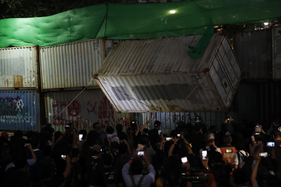 Protesters pull down a shipping container used as a barricade in front of the Grand Palace Saturday, March 20, 2021, in Bangkok, Thailand. Thailand's student-led pro-democracy movement is holding a rally in the Thai capital, seeking to press demands that include freedom for their leaders, who are being held without bail on charges of defaming the monarchy. (AP Photo/Sakchai Lalit)