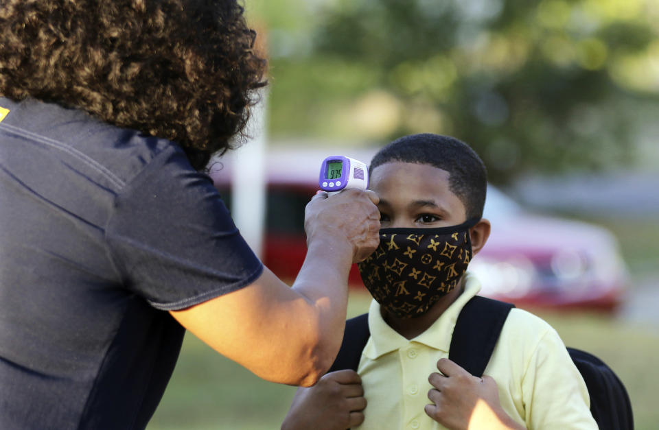 FILE - In this Monday, Aug. 24, 2020, file photo, fifth-grader Marcques Haley, gets his temperature checked by school nurse Rachel White before entering Stephens Elementary School in Little Rock, Ark. Most Arkansas public school students will be required to wear masks when 2001 classes begin in mid-August 2021, following moves by dozens of districts in response to a judge blocking the state's mask mandate ban. (Tommy Metthe/The Arkansas Democrat-Gazette via AP, File)