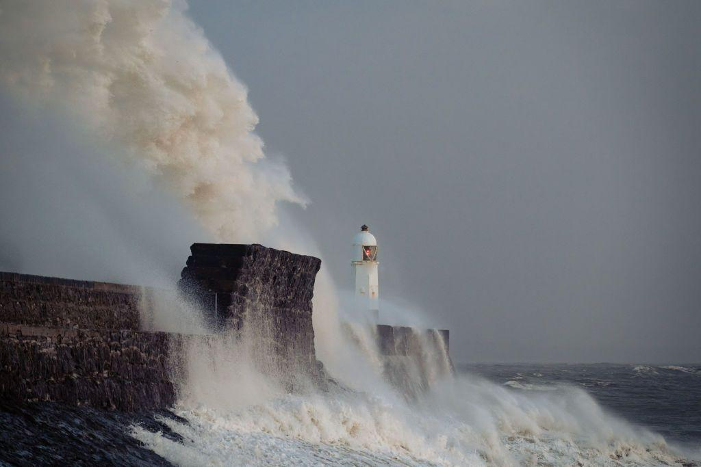 <p>Stormy waves crash against a harbour wall on the south coast of Wales. </p>