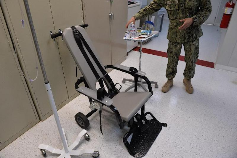 """This photo reviewed by the US military and taken during an escorted visit shows a US naval medic explaining the """"feeding chair"""" procedures at the  detention facility in Guantanamo Bay, Cuba, April 9, 2014"""