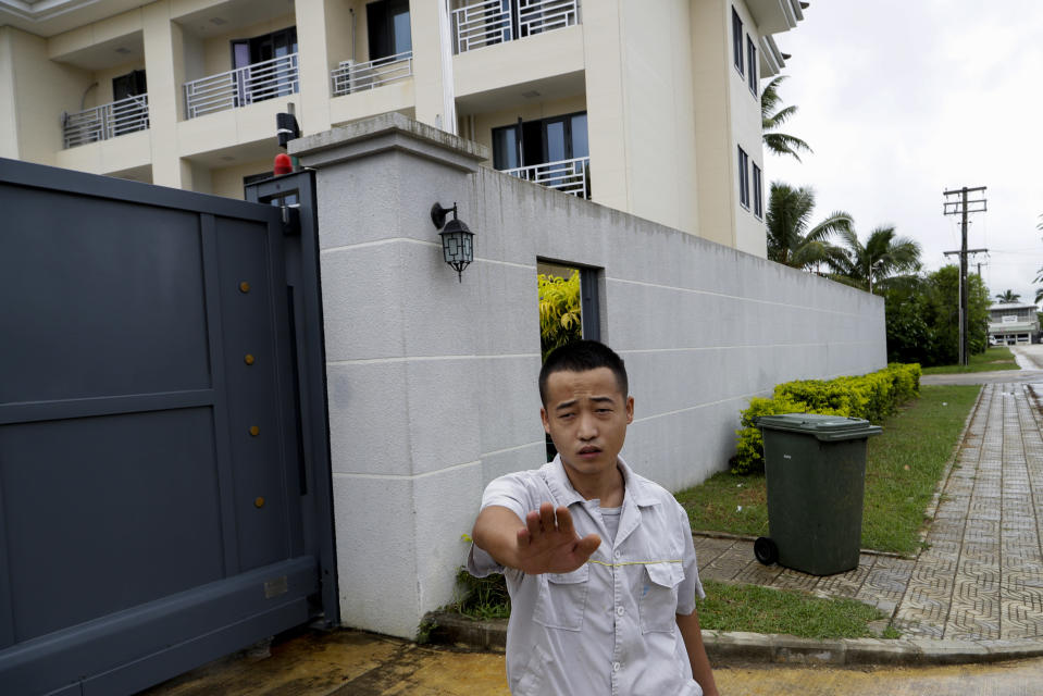 In this Monday, April 8, photo, a Chinese Embassy staff member gestures to stop taking photos outside the embassy accommodation building in Nuku'alofa, Tonga. China is pouring billions of dollars in aid and low-interest loans into the South Pacific, and even in the far-flung kingdom of Tonga there are signs that a battle for power and influence among much larger nations is heating up and could exact a toll. (AP Photo/Mark Baker)