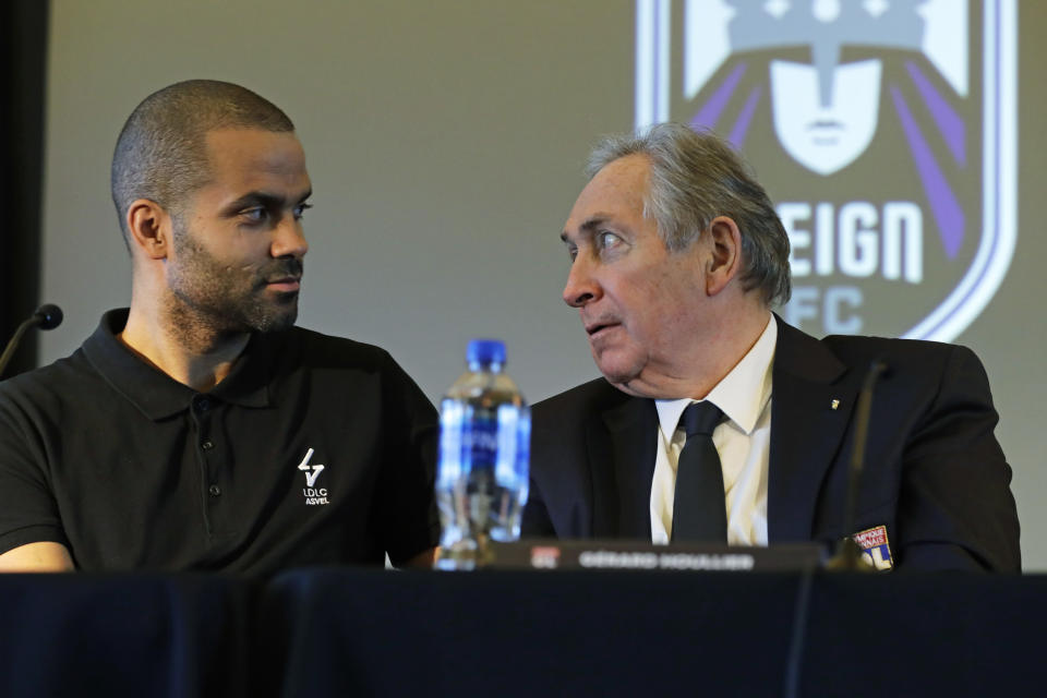 OL Groupe's Gerard Houllier, right, talks with former NBA basketball star Tony Parker, left, Thursday, Dec. 19, 2019, during a news conference to announce that OL Groupe, the parent company of Olympique Lyonnais, is buying the National Women's Soccer League's Reign FC team in a transaction expected to close in January 2020. Parker will be a minority owner of the team and Reign FC will continue to play its home games at Cheney Stadium, the venue it shares with the Triple-A minor league baseball team the Tacoma Rainiers. (AP Photo/Ted S. Warren)