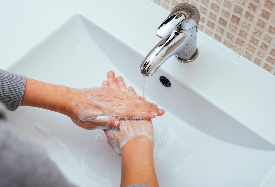 Woman wash her hands with soap and water in the bathroom of the house