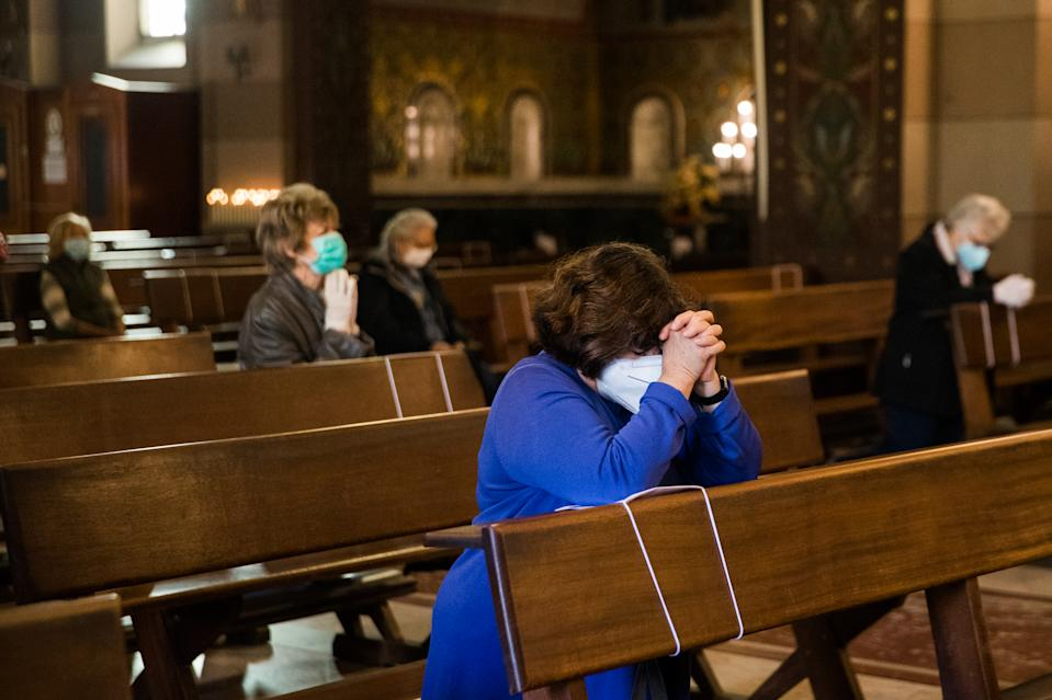 People pray in church in the first day when religious services are allowed again in Turin on May 18, 2020 during the country's lockdown aimed at curbing the spread of the COVID-19 infection, caused by the novel coronavirus. - Generic shops  and churches reopen in Italy on May 18, 2020 as new government disposition easing the lockdown in a cautious, gradual return to normality, allowing businesses and churches to reopen after a two-month lockdown. (Photo by Mauro Ujetto/NurPhoto via Getty Images)