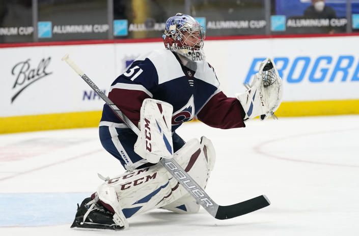Colorado Avalanche goaltender Philipp Grubauer makes a glove save of a shot from the Minnesota Wild in the second period of an NHL hockey game Saturday, March 20, 2021, in Denver. (AP Photo/David Zalubowski)