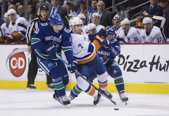 Vancouver Canucks' Bo Horvat, left, reaches for the puck as Nikolay Goldobin, right, of Russia, checks New York Islanders' Jordan Eberle during the first period of an NHL hockey game Saturday, Feb. 23, 2019, in Vancouver, British Columbia. (Darryl Dyck/The Canadian Press via AP)