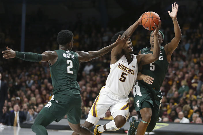 Minnesota's Marcus Carr, center, handles the ball through the defense of Michigan State's Rocket Watts (2) and Cassius Winston, right, during an NCAA college basketball game Sunday, Jan. 26, 2020, in Minneapolis. (AP Photo/Stacy Bengs)
