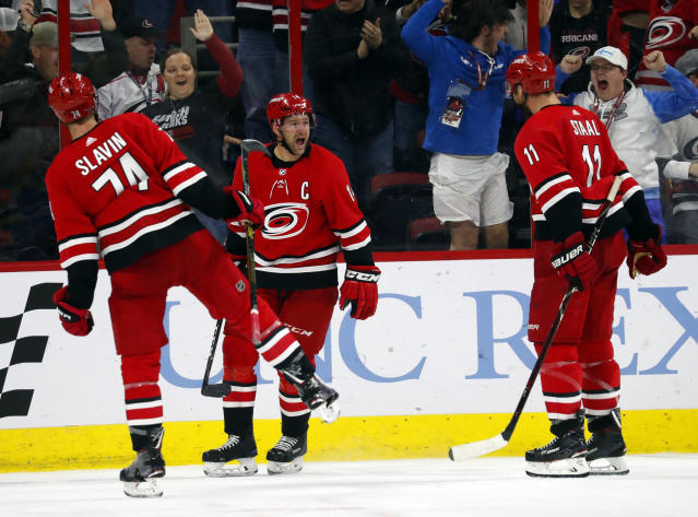 Carolina Hurricanes' Justin Williams (14) celebrates his goal against the Pittsburgh Penguins with teammates Jaccob Slavin (74) and Jordan Staal (11) during the third period of an NHL hockey game, Tuesday, March 19, 2019, in Raleigh, N.C. Hurricanes won 3-2 by shoot out. (AP Photo/Karl B DeBlaker)