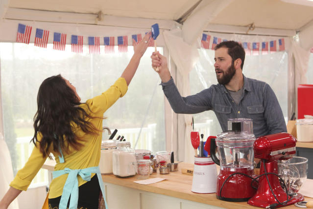 """Contestants Whitney Appleton Beery and James Reddick find time amidst the pressure to hi-five one another on a bake well done during a timed challenge on """"The American Baking Competition,"""" premiering Wednesday, May 29 (8:00-9:00 PM, ET/PT) on CBS."""