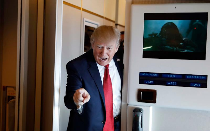 President Donald Trump points to a reporter as he meets reporters on Air Force One - Credit: AP