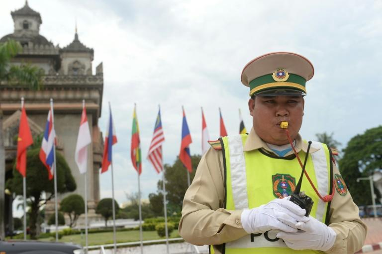 A policeman directs traffic in Vientiane on July 23, 2016, as Laos hosts the 49th South East Asian Nations (ASEAN) meeting