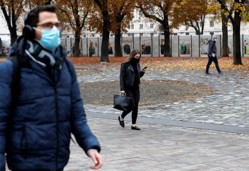 People wearing protective face masks walk in downtown Budapest