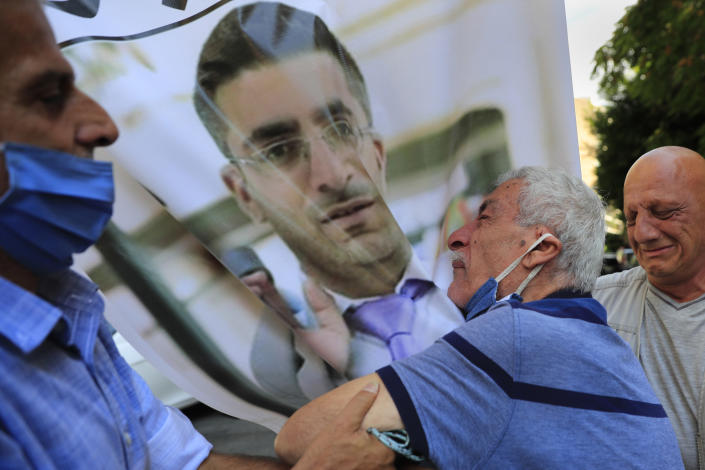 The father of Ibrahim Harb, 35, center, a Lebanese man who was critically injured in the massive explosion at Beirut's port last year and who died on Monday nearly 14 months after the blast, mourns on his son's portrait during his funeral procession, in Beirut, Lebanon, Tuesday, Sept. 28, 2021. On Aug. 4, 2020, hundreds of tons of ammonium nitrate, a highly explosive material used in fertilizers, ignited after a massive fire at the port. The death brings to at least 215 the number of people who have been killed by the blast, according to official records. (AP Photo/Hussein Malla)