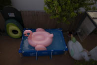 "A big inflatable flamingo floats in a plastic portable pool in a private patio in Seville, Spain on Aug. 11, 2020. Maria Luque bought the pool ""because I have problems with my back and couldn't go to the gym in the middle of the coronavirus pandemic"". Searching for a solution to keep cool, portable pools have become the newest fad, taking over backyards, terraces, communal patios and even the streets of hot spots like Seville, in the country's south. (AP Photo/Laura Leon)"