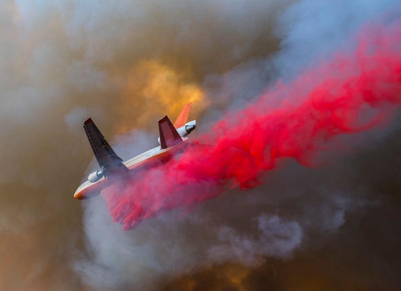 The DC-10 VLAT, or Very Large Air Tanker, makes a drop between Santiago Canyon Road and Cowan Heights while trying to slow the spread of the Canyon Fire 2 in Anaheim Hills, California.