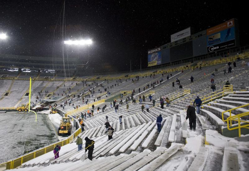 Hundreds of people shovel snow from the seating sections at Lambeau Field as snow falls Thursday, Jan. 17, 2008, in Green Bay, Wis. The Green Bay Packers face the New York Giants in the NFC Championship football game Sunday, Jan. 20, 2008, at Lambeau Field. (AP Photo/Morry Gash)
