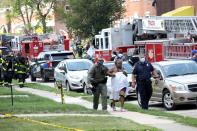 Police officers help a woman at the scene of an explosion in a residential area of Baltimore