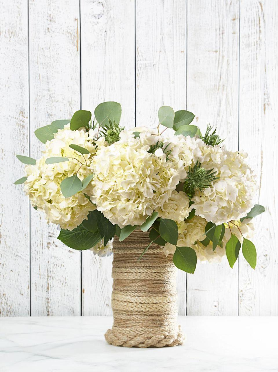 """<p>Add a nautical vibe to your centerpiece with a few lengths of jute rope. The trick: Flip the vase upside down and work from base to mouth. Toss in a beachy bunch of white hydrangeas, and you're ready for a clambake! </p><p><em><a href=""""https://www.goodhousekeeping.com/home/craft-ideas/how-to/g597/diy-vase-upgrades/?slide=4"""" rel=""""nofollow noopener"""" target=""""_blank"""" data-ylk=""""slk:Get the tutorial »"""" class=""""link rapid-noclick-resp"""">Get the tutorial »</a></em> </p>"""