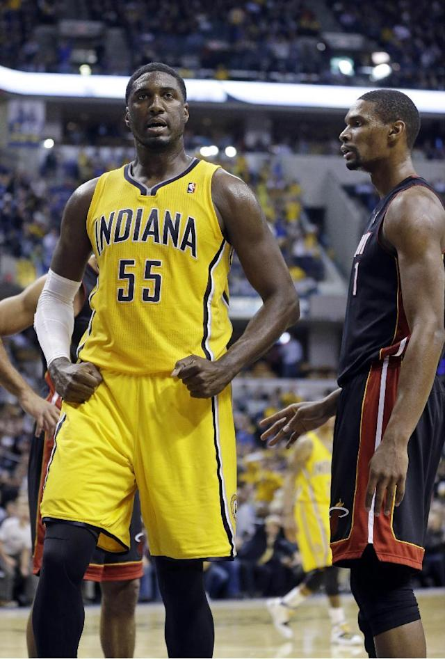 Indiana Pacers center Roy Hibbert, left, react to hitting a bucket as he was fouled by Miami Heat center Chris Bosh in the second half of an NBA basketball game in Indianapolis, Tuesday, Dec. 10, 2013. The Pacers won 90-84. (AP Photo/Michael Conroy)