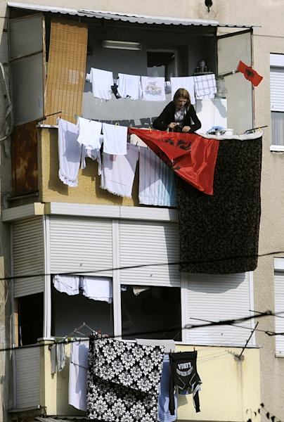 A woman is fixing an Albanian flag with the laundry on a balcony in Skopje, Macedonia, on Saturday, Nov.24, 2012. Macedonian capital Skopje, particularly the parts populated with ethnic Albanians, are flooded with Albanian flags, in the eve of the celebration of 100 years of Albania's independence and the national flag. Ethnic Albanians make up a quarter of Macedonia's 2.1 million people and are the largest ethnic minority in the country. (AP Photo/Boris Grdanoski)