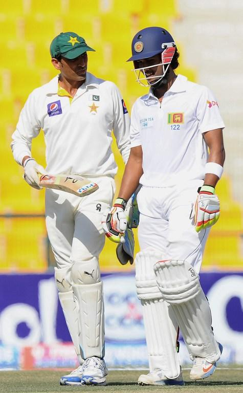 Sri Lankan batsman Dinesh Chandimal (R) shares a light moment as he speaks with Pakistan wicketkeeper Younis Khan (L) during the fourth day of the first cricket Test match between Pakistan and Sri Lanka at the Sheikh Zayed Stadium in Abu Dhabi on January 3, 2014. Pakistan's last six wickets fell cheaply on the third morning of the first Test and restrict them to 383. Sri Lanka were bowled out for 204 in their first innings of the first Test against Pakistan in Abu Dhabi. AFP PHOTO/Ishara S. KODIKARA