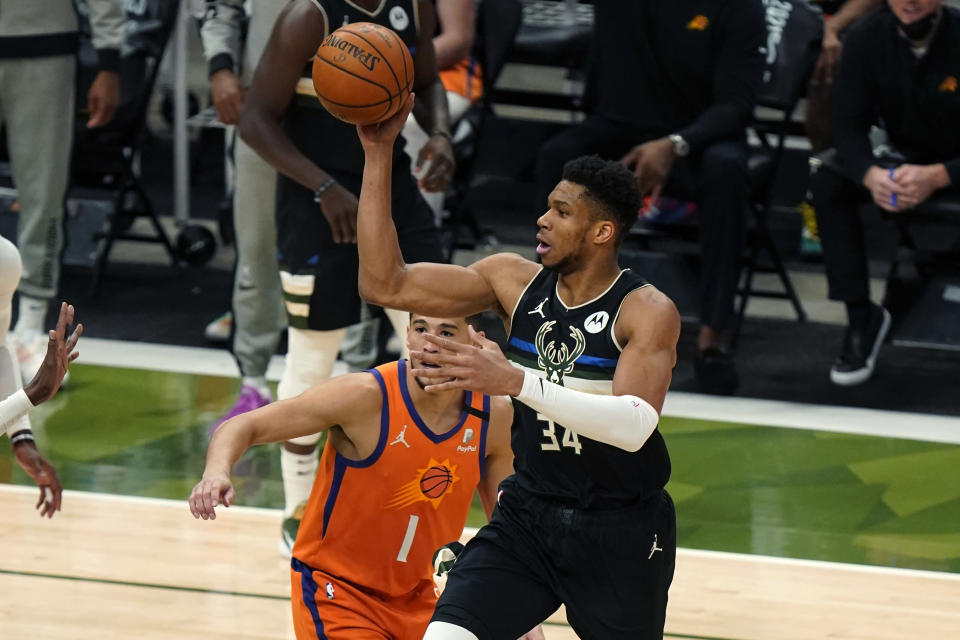 Milwaukee Bucks forward Giannis Antetokounmpo (34) moves towards the basket against Phoenix Suns guard Devin Booker (1) during the first half of Game 6 of basketball's NBA Finals in Milwaukee, Tuesday, July 20, 2021. (AP Photo/Paul Sancya)