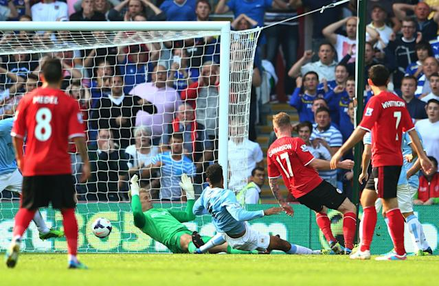 CARDIFF, WALES - AUGUST 25: Aron Gunnarsson #17 of Cardiff scores to level the scores at 1-1 during the Barclays Premier League match between Cardiff City and Manchester City at Cardiff City Stadium on August 25, 2013 in Cardiff, Wales. (Photo by Michael Steele/Getty Images)