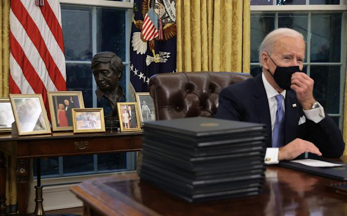 Joe Biden prepares to sign a series of executive orders at the Resolute Desk in the Oval Office - Getty