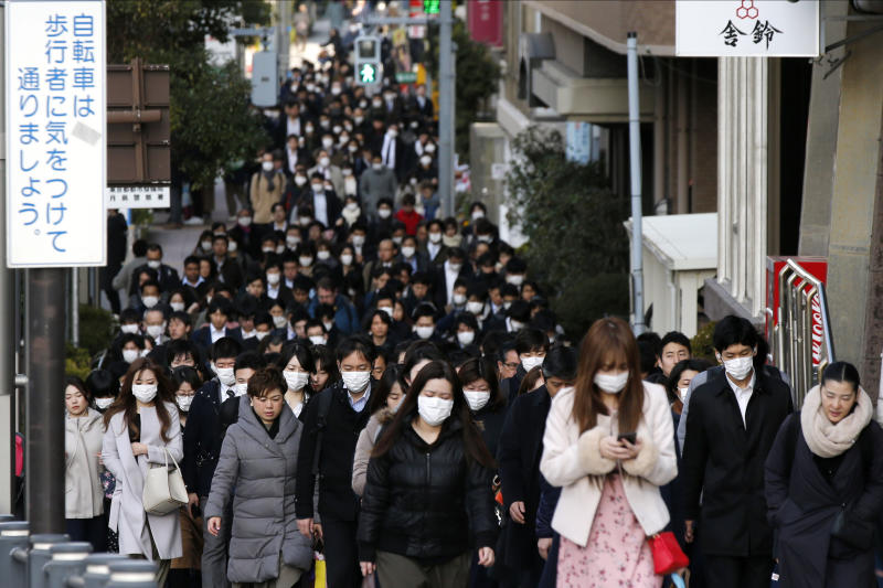 FILE - In this Feb. 20, 2020, file photo, people wear masks as they commute during the morning rush hour, in Chuo district in Tokyo. When the Japanese government declared an emergency to curb the spread of the coronavirus earlier April and asked people to work from home, crowds rushed to electronics stores. Many Japanese lack the basic tools needed to work from home. Contrary to the ultramodern image of Japan Inc. with its robots, design finesse and gadgetry galore, in many respects the country is technologically challenged. (AP Photo/Kiichiro Sato, File)